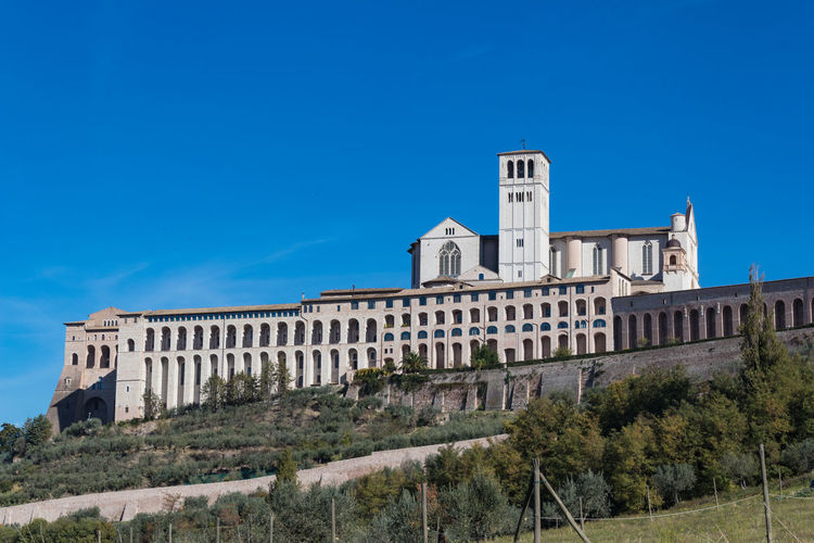 Abbey Basilica Church Saint Francis Of Assisi Architecture Blue Building Exterior Built Structure Clear Sky Day History Italy Low Angle View Nature No People Outdoors Sky Travel Destinations Tree Umbria