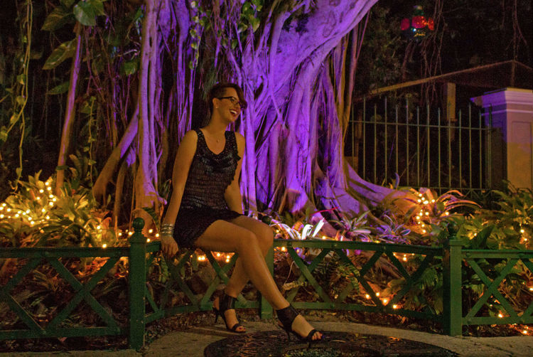 Woman Sitting On Fence By Illuminated Trees And Plants
