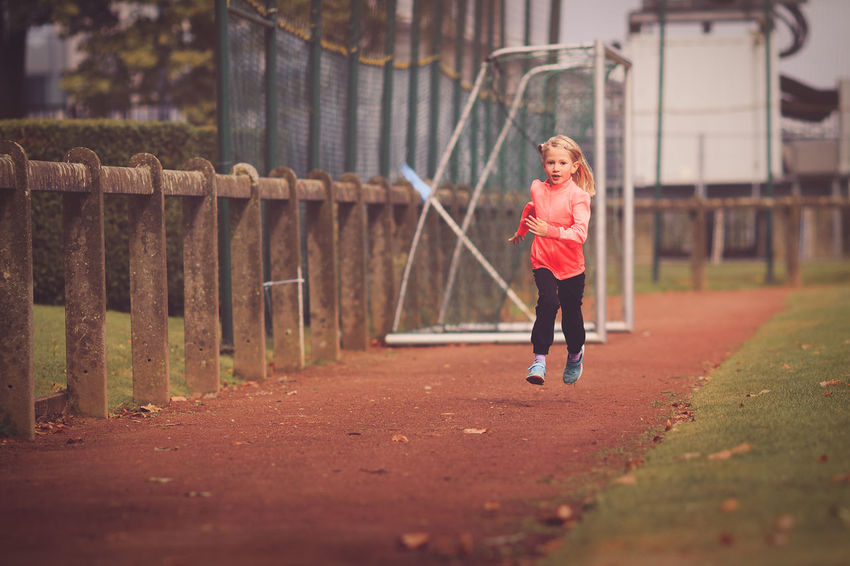 Exercising Running Age 6-9 Assertiveness Challenge Day Discipline Europe Full Length Lifestyles One Person Outdoors People Perseverance Real People Running Running Track Sports Clothing Sports Race Track Young Girl