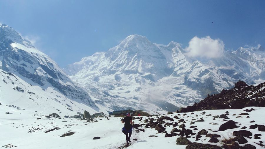 Person walking against snowcapped mountains