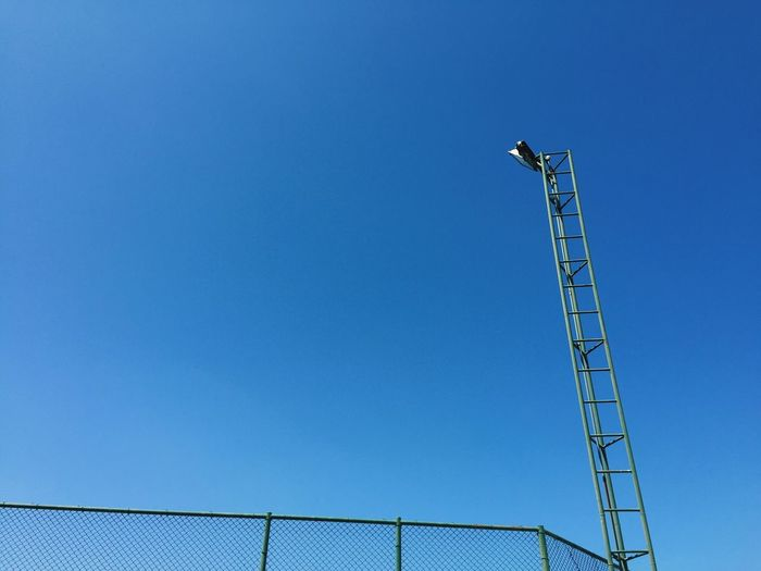 Low angle view of lighting equipment against clear blue sky on sunny day