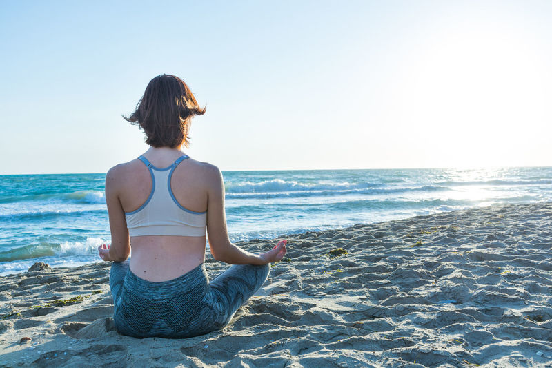 Rear View Of Woman Meditating At Beach Against Sky