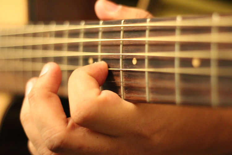 Cropped hand of musician playing guitar