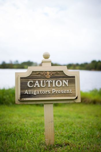 Close-up of information sign on grass by lake against sky