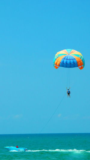 Man paragliding over sea against clear blue sky