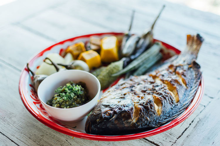 High angle view of fish with vegetables served on wooden table