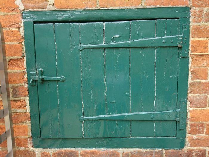 Old Green door or hatch in red brick wall Door Green Color Architecture Building Exterior Close-up EyeEmNewHere Old Door Hatchbdoor Secret Door Character