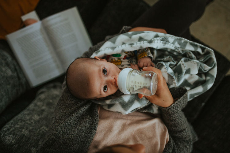 Directly above shot of woman feeding milk to baby boy at home