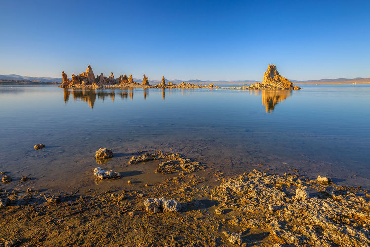 The popular calcareous tufa formation reflects on the smooth waters of Mono Lake, one of the oldest lakes in North America. The Mono Lake Tufa State Natural Reserve, California, United States. United States Land Panorama Yosemite Yosemite National Park National Park Nature USA America Mono Lake California Lake Water Sky Tranquility Clear Sky Architecture Tranquil Scene Built Structure Scenics - Nature Beach Day Beauty In Nature No People Sea Reflection Blue Travel Destinations Rock