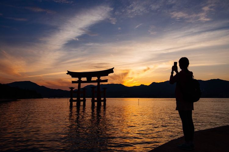 Person Taking Picture Of Torii Gate At Sunset