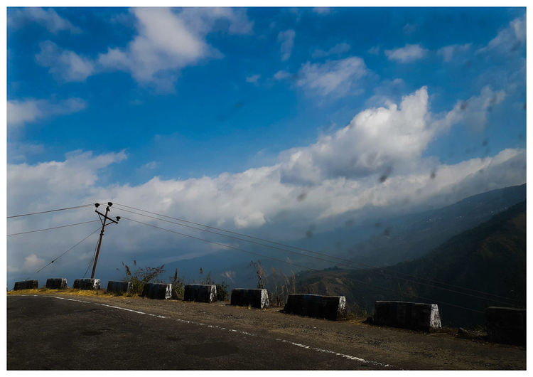 Road by mountains against sky