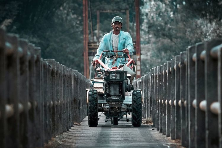 Portrait of man riding tractor on road