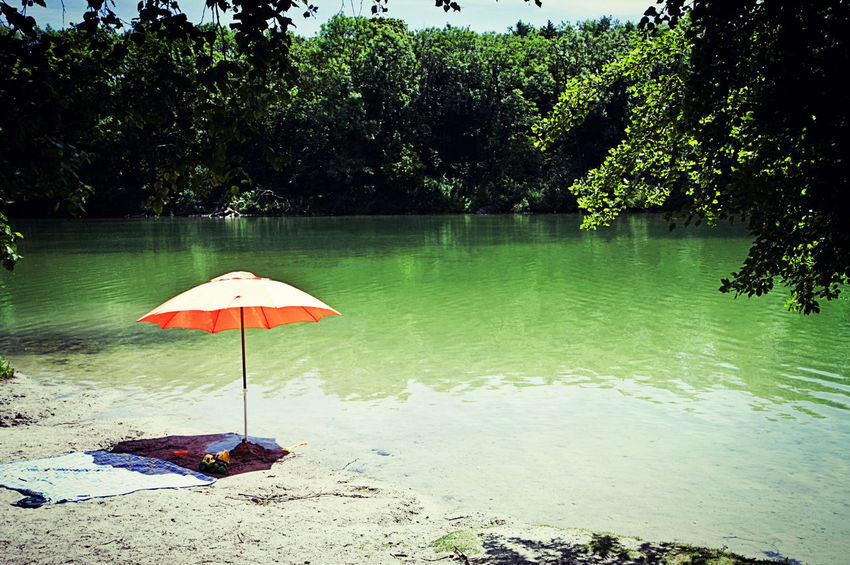 Orange sunshade for a quiet summer relax on the shore of Poschinger Weiher lake near Munich Beauty In Nature Day Green Holiday Lake Lakeshore Leisure Activity Nature No People Orange Outdoors Parasol Relax Scenics Sky Summer Sunbathing Sunlight Sunshade Tranquility Tree Vacation Warm Water
