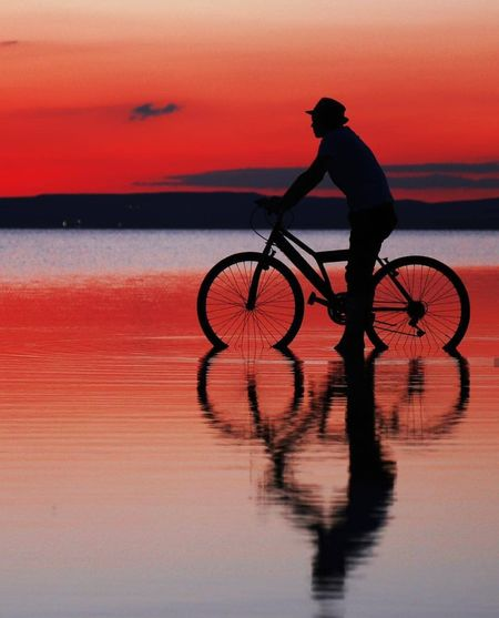 Silhouette man riding bicycle at sea against sky during sunset