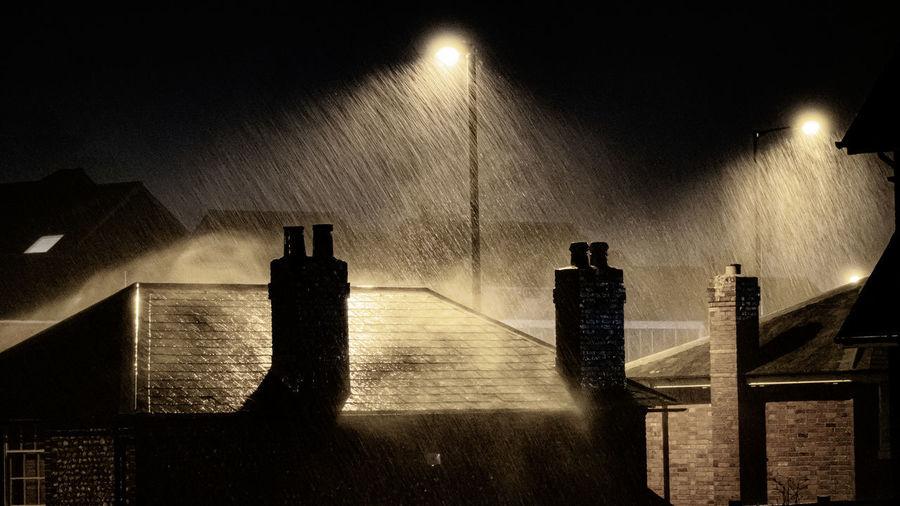 Illuminated street light by building against sky at night