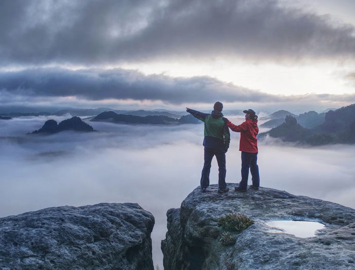 Lovers mirroring in water eye at mountain summit above thick mist. climbing couple at top of summit