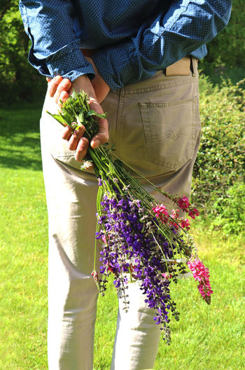 rear view of a man in a garden, holding a bunch of multi colored wildflowers behind his back Wildflowers Flowers Bunch Bouquet Color Beautiful Man Hand Holding Hiding Surprise Behind Rear View Gift Romance Background Copy Space Close-up Love Natural Nature Plant Growth Freshness Fragility Multi Colored Purple Pink White Green Grass Lawn Meadow Garden Sunlight Springtime Summer Season  Outdoors Day Nobody Retro Vintage