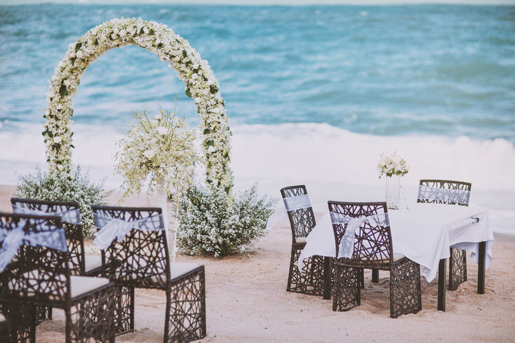 Beach wedding venue setting with flower, floral decoration on arch. Married registration table arrangment on the sand with panoramic ocean view Banquet Married Nature Setting Sun Setup Thailand Venue Wedding Arch Arrangement Beach Bouquet Certificate Coast Decoration Floral Flower Island Marriage  Ocean Preparation  Registration Sand Scenics Sky