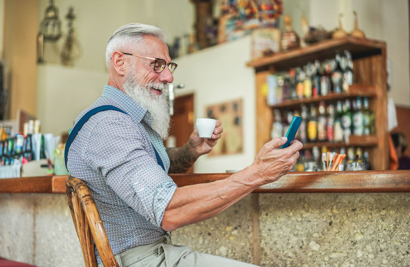 Hipster senior man using smartphone while drinking coffee One Person Communication Wireless Technology Adult Mobile Phone Men Lifestyles Smart Phone Senior Men Technology Senior Adult Glasses Gray Hair Eyeglasses  Coffee Bar Cappuccino