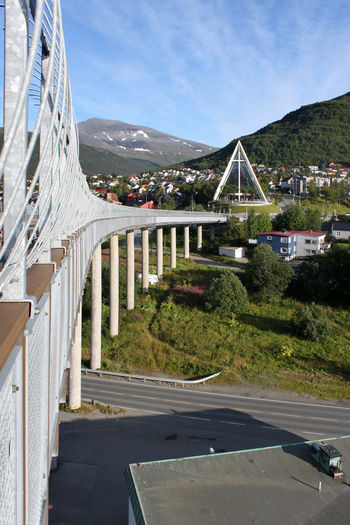View along the handrail of Tromsøbrua bridge towards Ishavskatedralen church in Tromso, Norway Balustrade Basilica Bridge - Man Made Structure Cathedral Church Column Concrete Construction Contemporary Curved  Eismeerkathedrale Glass Facades Guardrail Handrail  Ishavskatedralen Modern Architecture Modernism Norway Pillars Postmodern  Postmodernism Row Sacral Building Tromsobrua Tromsø