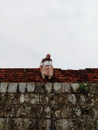 Low angle view of woman standing against wall