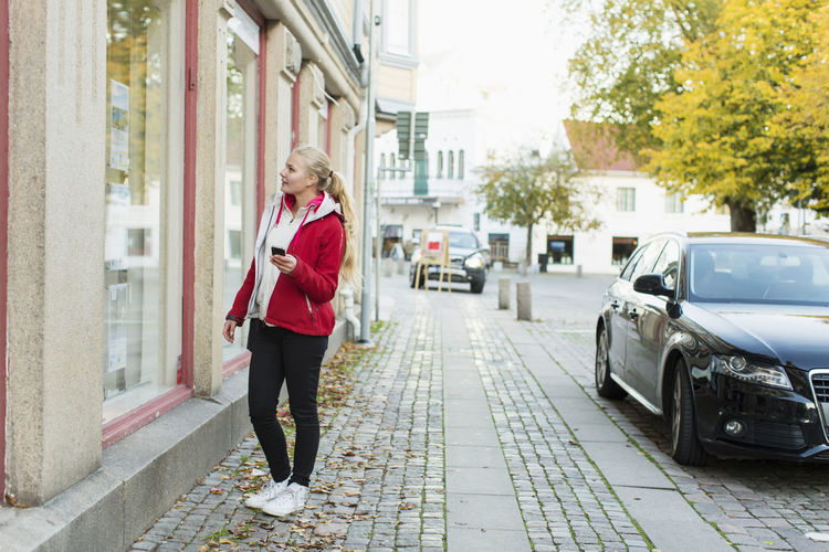 Woman standing on footpath in city