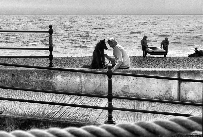 Animal Themes Beach Black And White Blackandwhite Boy And Dog Full Length Horizon Over Water Leisure Activity Lifestyles Men Nature Person Pier Railing Rear View Sea Shore Sitting Standing Togetherness Water Fine Art