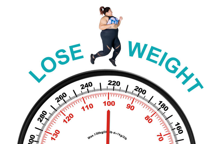 Digital composite image of woman running over weight scale with text against white background