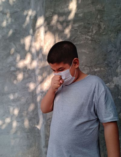 Low angle view of boy wearing flu mask coughing while standing by wall outdoors