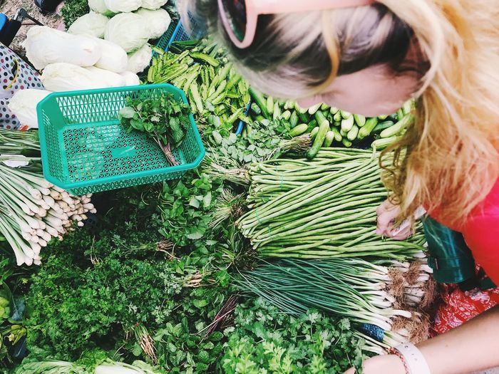 High angle view of woman holding vegetables in market
