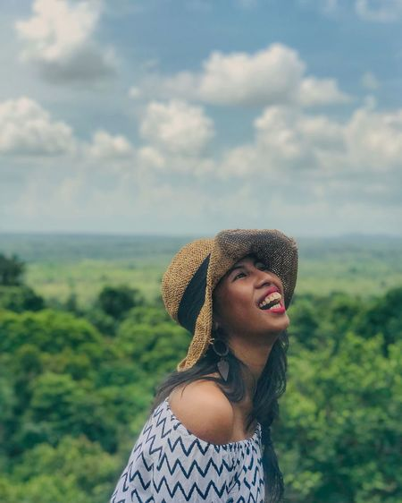 Young woman wearing hat laughing against landscape