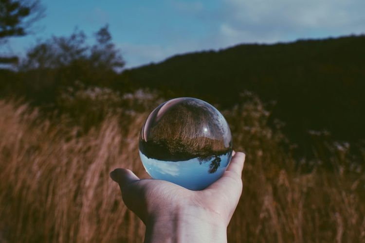 Cropped hand holding crystal ball against mountain with reflection