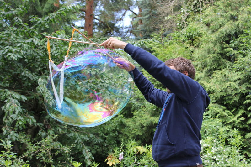 Making bubbles Adult Big Bubble Bubble Casual Clothing Day Magic Nature One Person Playing Playing Adult Real People Soap Bubbles Standing Tree