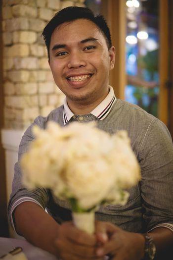 Portrait of smiling man holding flower bouquet