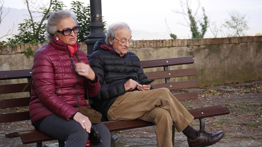 Senior couple wearing warm clothing while sitting on bench