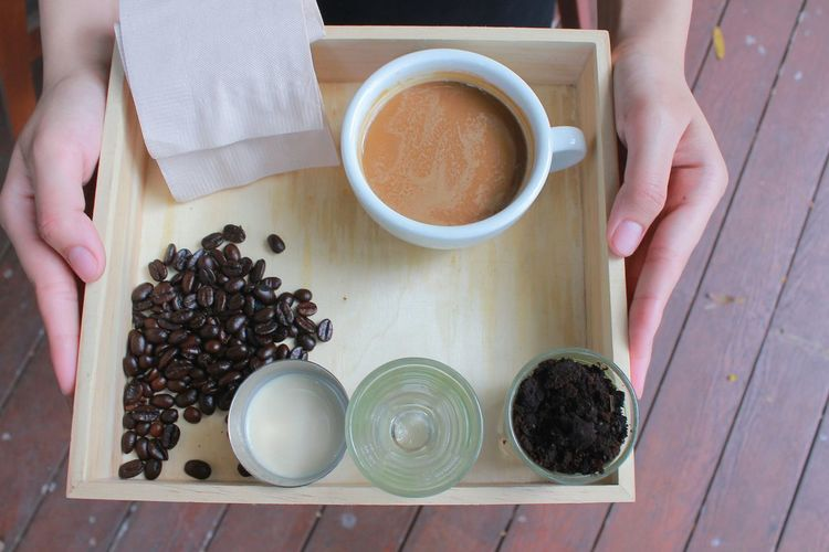High angle view of coffee cup and beans on tray