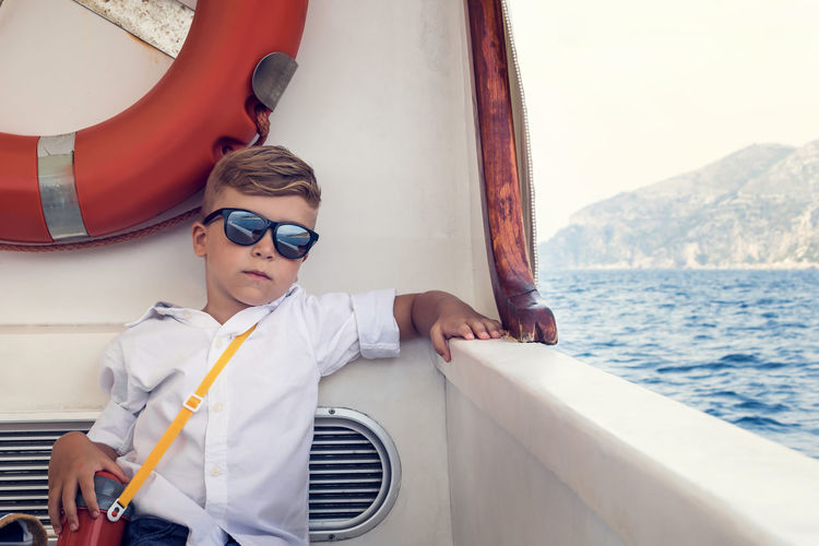 Portrait of cute boy wearing sunglasses while traveling in ship