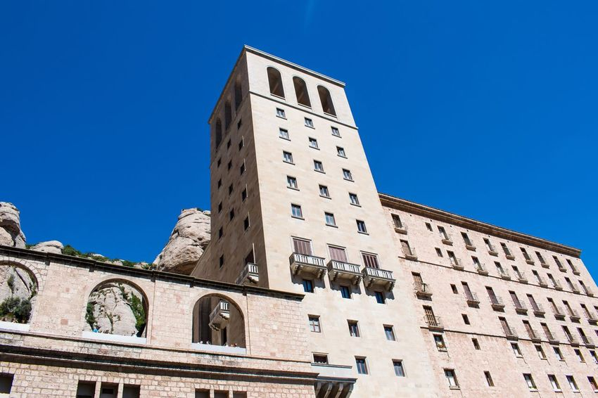 Eyeemphoto Color Palette Monastery Montserrat Barcelona Architecture Building Exterior Built Structure Low Angle View Blue Clear Sky Window Residential Building Residential Structure City Building Tall - High Tower Arch Day Outdoors Spire  Skyscraper Tall Apartment