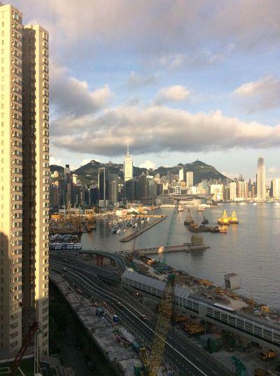 City Scape Morning Sunshine Hong Kong Harbour building works Roadway Skyscrapers opera house Blue Sky Hillside Cranes