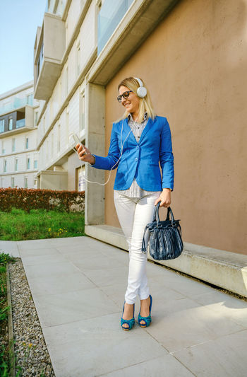 Businesswoman with headphones and mobile in the street Business Glasses Happy Headphones Sunlight Woman Worker Working Business Finance And Industry Businesswoman Caucasian Executive  Flare Lifestyles Office Building One Person Outdoors Portfolio Professional Real People Smart Phone Street Sun Vertical Young Adult