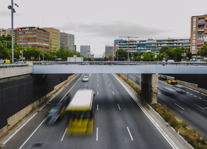 Road by bridge in city against sky