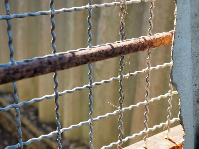 Close-up of rusty metal fence against wall
