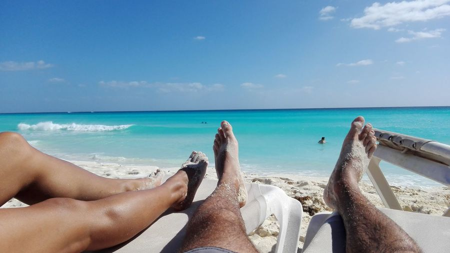 Low Section Of Man And Woman Relaxing On Beach Against Sky
