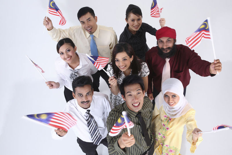 High angle portrait of smiling business people holding malaysian flag while standing over white background