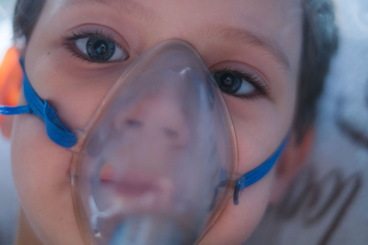 Close-up portrait of boy wearing oxygen mask