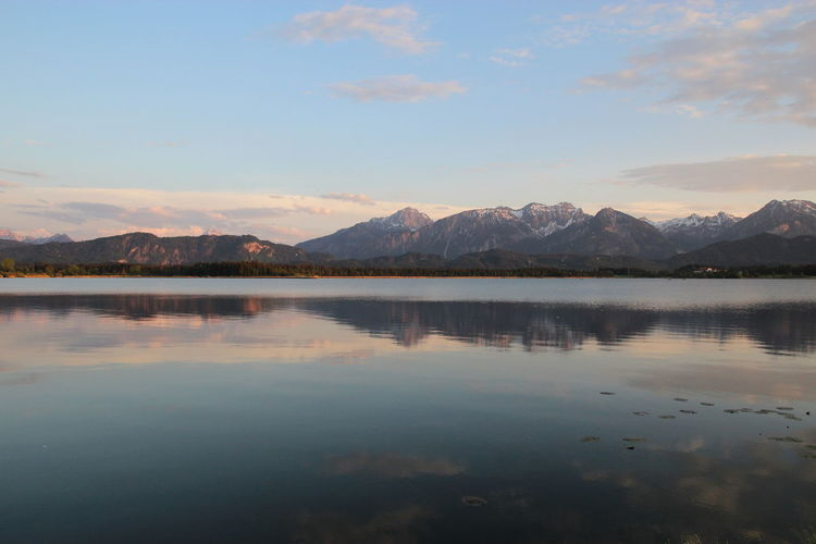 Scenic view of lake by mountains against sky