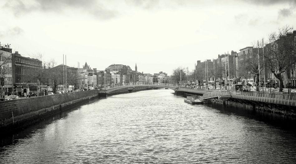 Ha Penny Bridge Over Liffey River In City Against Sky
