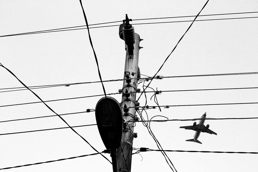 Cross the line with air plane Electricity Pylon Electricity  Power Line  Cable Aeroplane Connection Sky Low Angle View Wide Shot Photography Photographer Eyeemphotography Stockphoto Fotografi Stockphotography Golden Rule Market Minimalism Photo Blackwhite