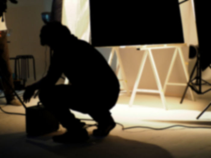 Blurry image behind the scenes of shooting video production in a studio with small set professional lighting equipment. Light Production Set Studio Close-up Film Industry Indoors  Studio; Photography; Set; Video; Film; Photo; Light; Equipment; Production; White; Camera; Professional; Technology; Background; Flash; Spotlight; Fashion; Lamp; Backdrop; Reflector; Photographic; Crew; Cable; Empty; Industry; Movie; Tripod; Black; Nobody