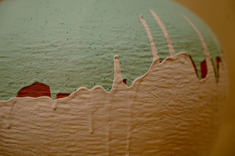 Close-up of ice cream on land against wall